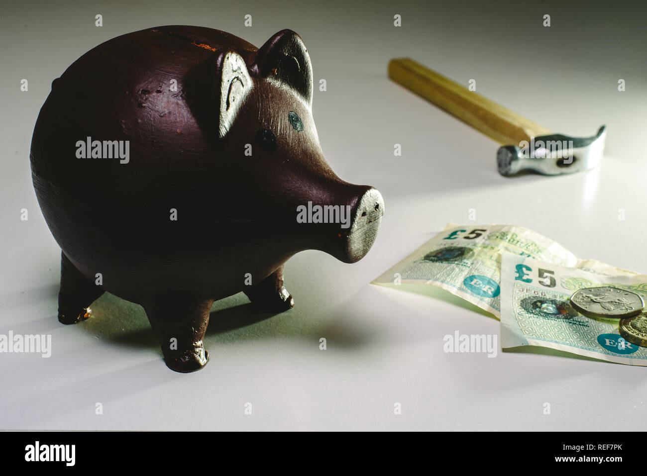 About to break piggy bank with English money to face savings in times of economic crisis. - Stock Image