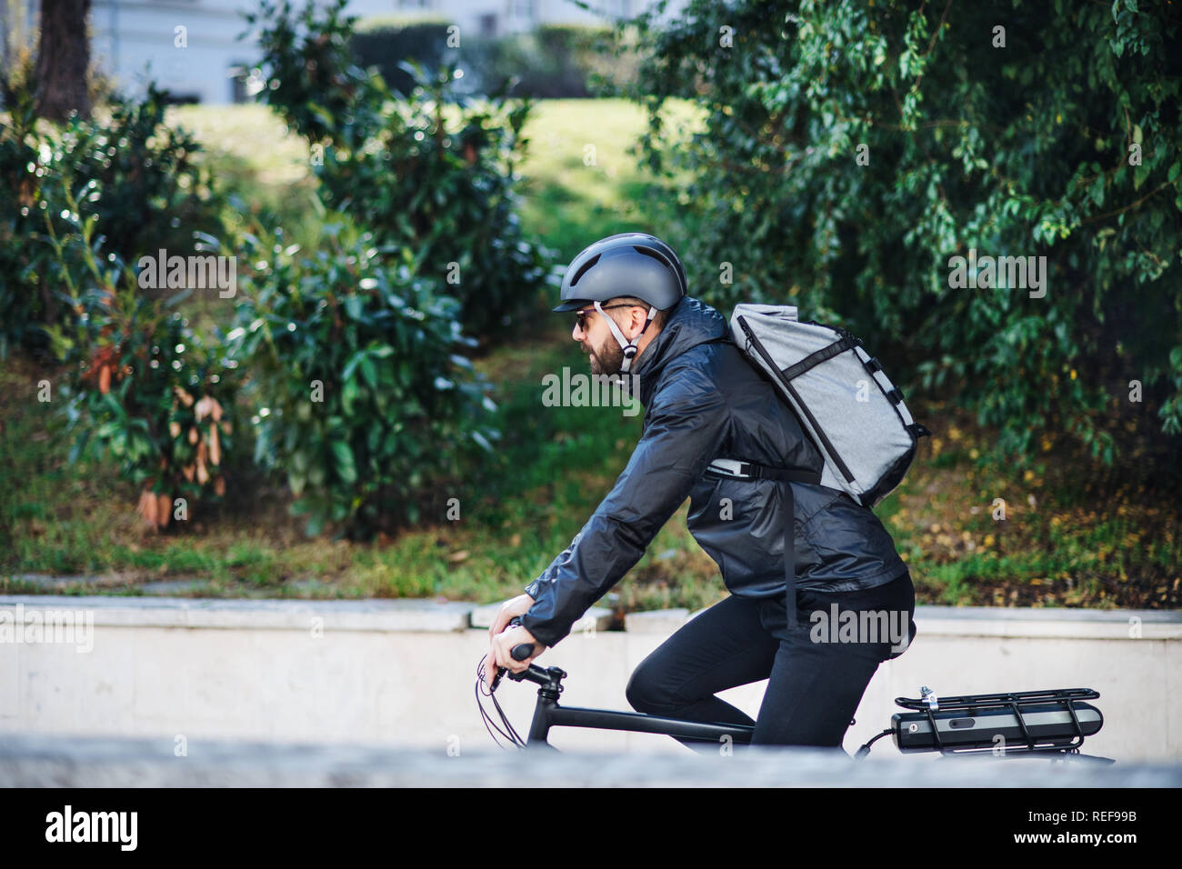 Male bicycle courier delivering packages in city. Copy space. Stock Photo