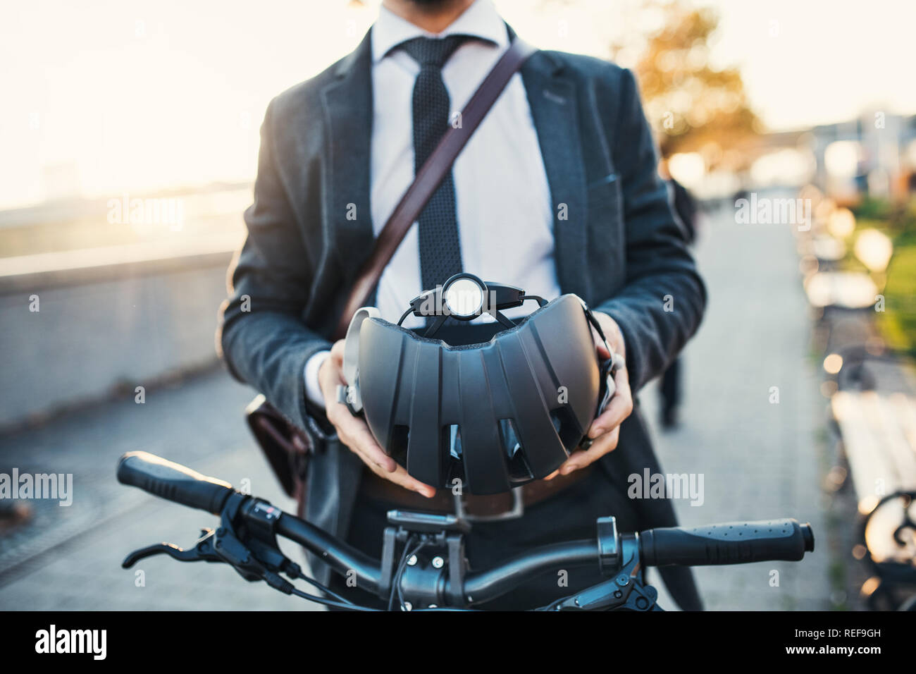 Midsection of businessman commuter with electric bicycle traveling from work in city. Stock Photo