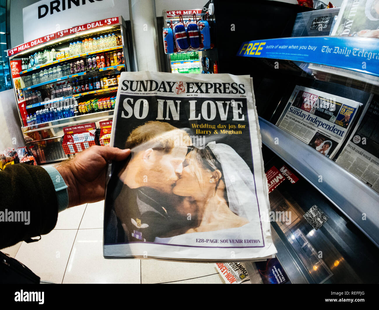 LONDON, ENGLAND - MAY 20, 2018: POV The Sunday Express front cover newspaper in British press kiosk featuring portraits of Prince Harry and Meghan Markle following the Royal Wedding So In Love - Stock Image