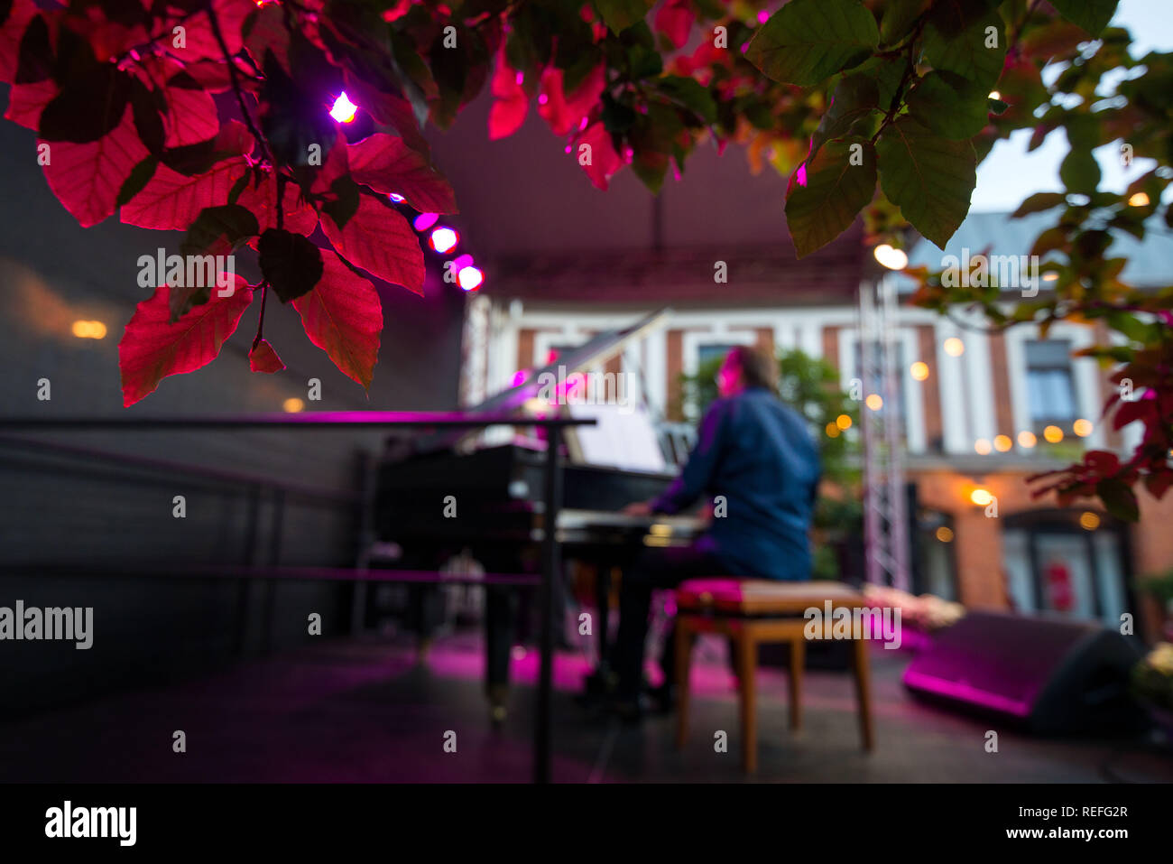 Male musician on stage playing piano. Crowded venue. Audience enjoying romantic and relaxing evening. - Stock Image