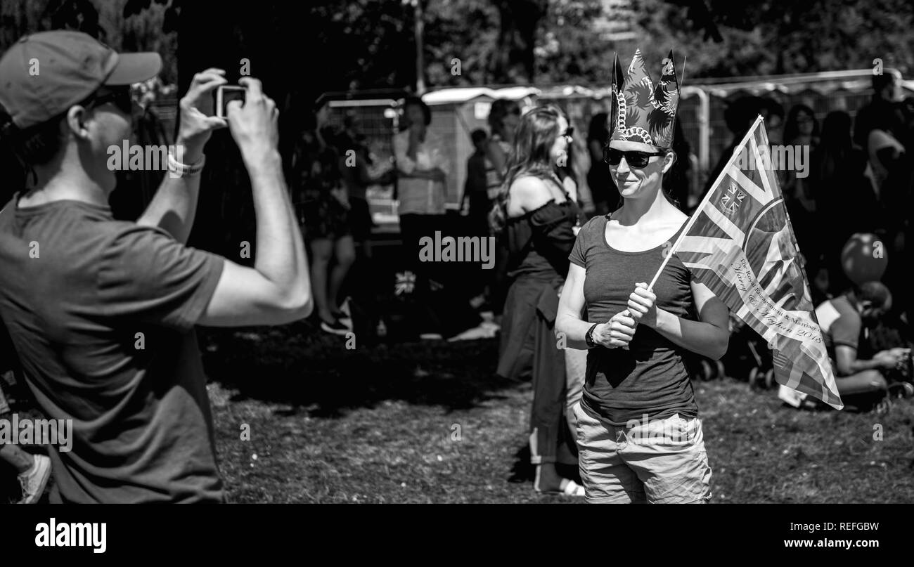 WINDSOR, BERKSHIRE, UNITED KINGDOM - MAY 19, 2018: Man taking photo of woman with flag at royal wedding marriage celebration of Prince Harry, Duke of Sussex and the Duchess of Sussex Meghan Markle - Stock Image