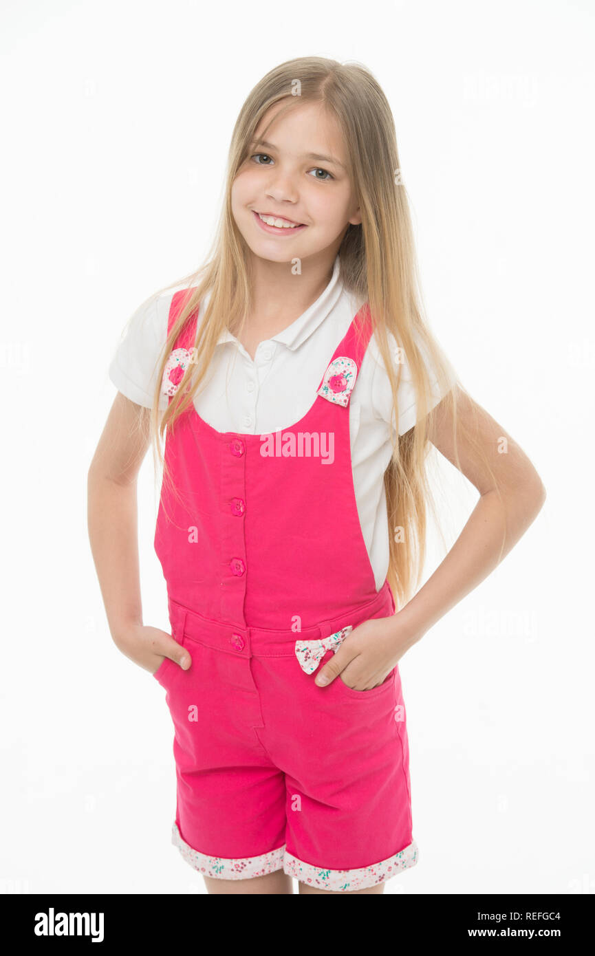 Happy childhood and childcare. Small girl smile in pink jumpsuit isolated on white. Child smiling with long blond hair. Kid model in fashionable overall. Fashion style and trend. - Stock Image