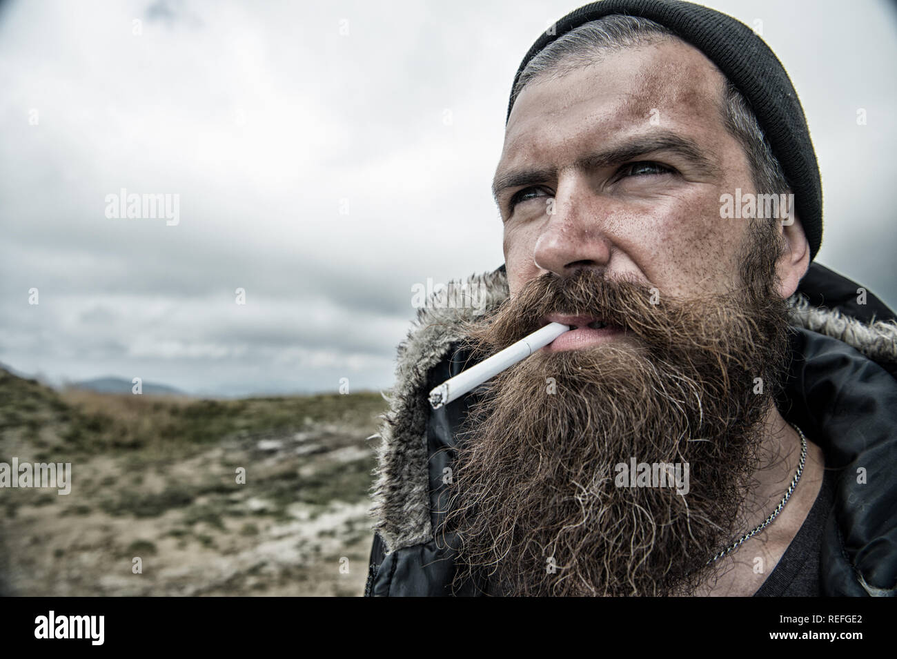 Man with long beard and mustache smoking cigaret. Brutality concept. Hipster on strict face with beard looks brutally while hiking and smoking. Man with brutal bearded appearance, untidy and unshaven. - Stock Image
