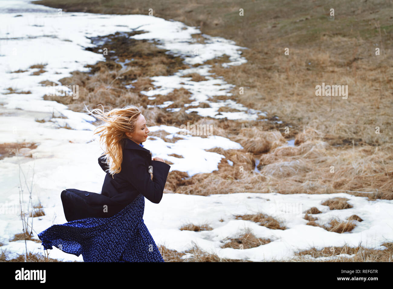 Woman running in the winter field Stock Photo