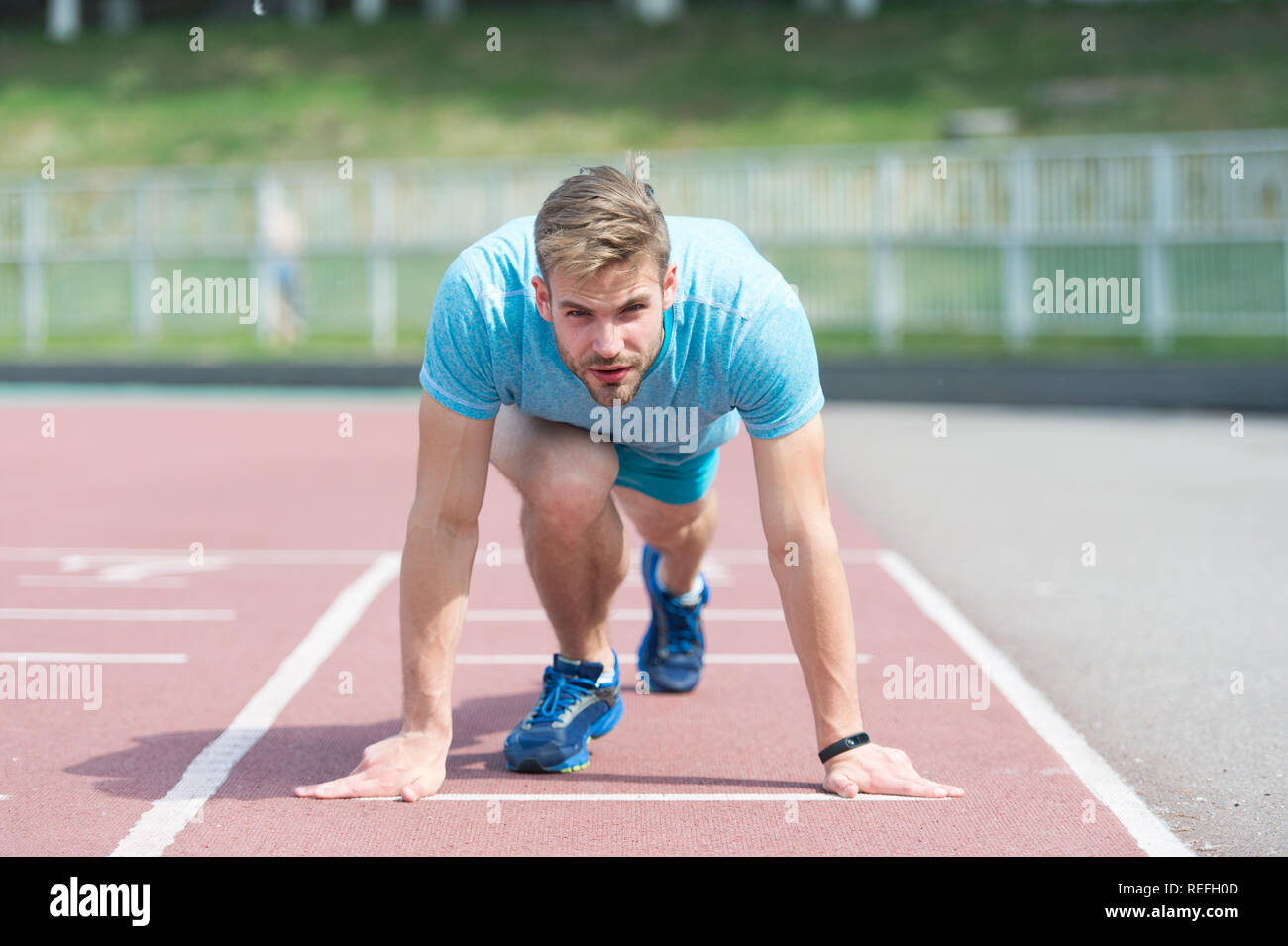 Man runner on start position at stadium. Runner in start pose on running surface. Man run outdoor at running track. Sport and athletics concept. Sportsman on concentrated face ready to go. Stock Photo