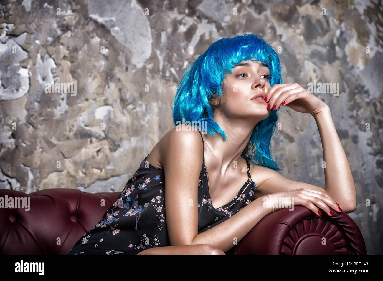 Lady on thoughtful face posing in blue wig, concrete wall background. Woman with blue hair looks unordinary and extraordinary. Freak concept. Lady freak with unordinary appearance. - Stock Image
