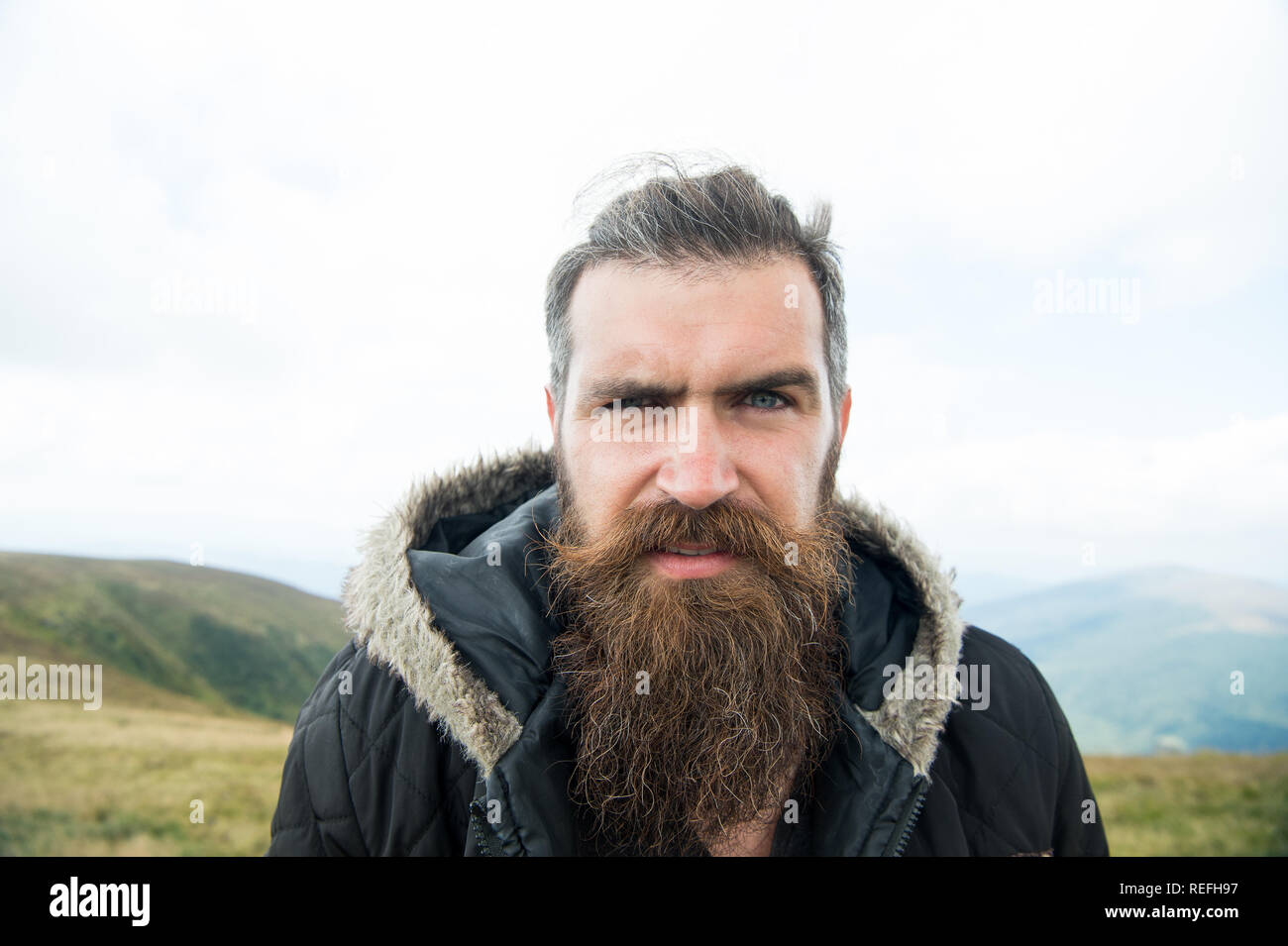 Man with long beard and mustache wears jacket. Hipster on strict face with beard looks brutally while hiking. Hermit concept. Man with brutal bearded appearance, brutal unshaven man looks untidy. - Stock Image