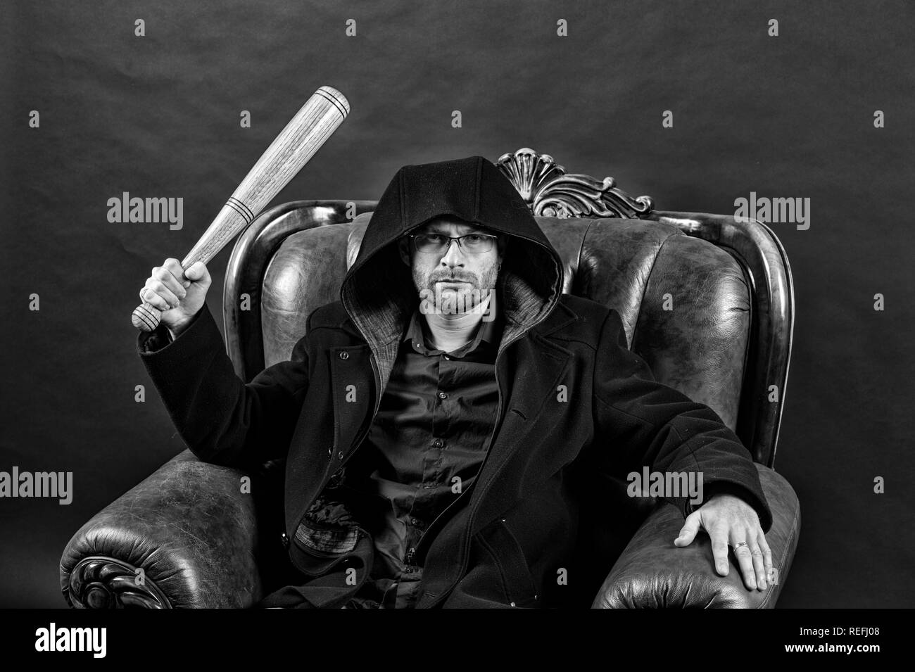 Gangster guy strike with bat weapon. Bearded man with baseball bat sit in armchair. Criminal wear hood in coat. Crime or aggression and violence concept, black and white. - Stock Image