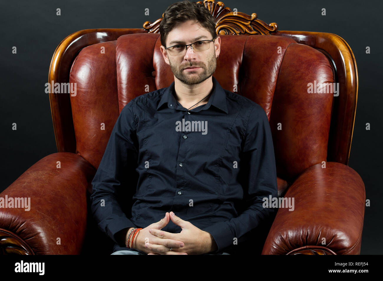 Man relax in brown leather armchair. Macho with beard on unshaven face. Bearded man wear shirt and glasses. Barber salon and skincare. Fashion accessory and furniture. - Stock Image