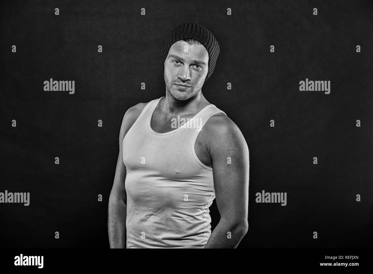 Sportsman with bristle on serious face. Man stand with strong arms on dark background. Macho in trendy vest and hat. Sport and fitness. Fashion style and trend, black and white. - Stock Image