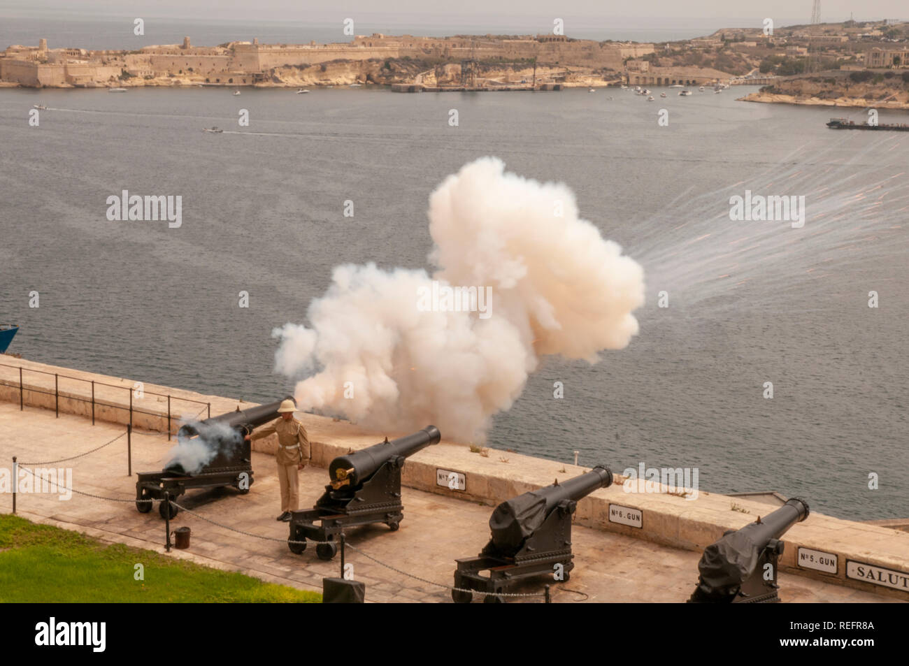 Soldier firing an old bronze cannon for the midday salute at the Saluting Battery at Upper Barrakka Gardens, Valletta, Malta. - Stock Image