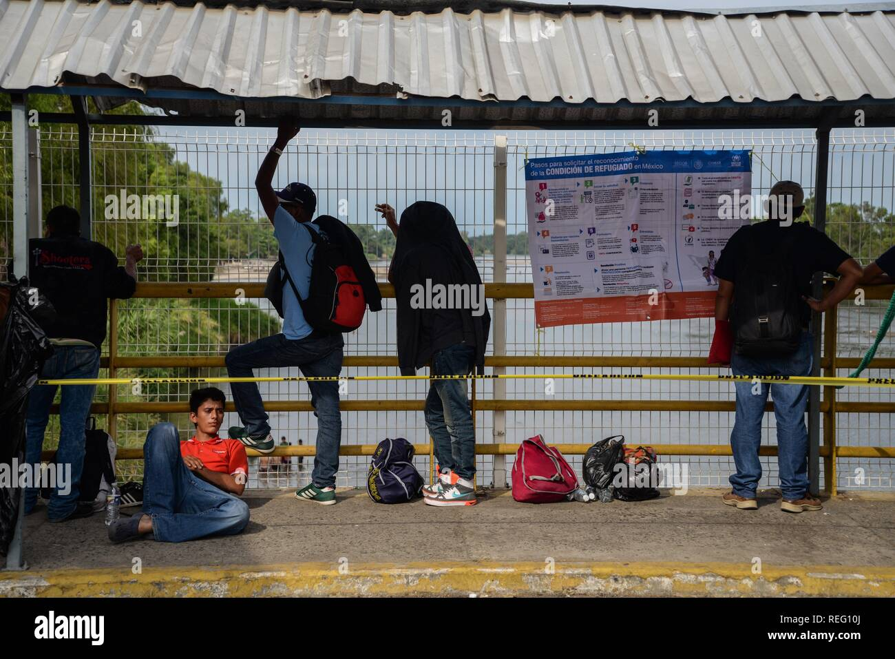 Honduran migrants who have decided to accept the humanitarian card, wait on the bridge that crosses the river Suchiate to enter Mexican territory through the city of Hidalgo, on 21 January 2019, where they will be allowed to look for work or go to the border with the United States to try to cross. Around 400 Hondurans started another caravan today with the idea of crossing Guatemala and arriving in the United States, a week after another group of more than 2,000 nationals left the country and many of them are waiting to enter Mexico. EFE/Luis Villalobos - Stock Image