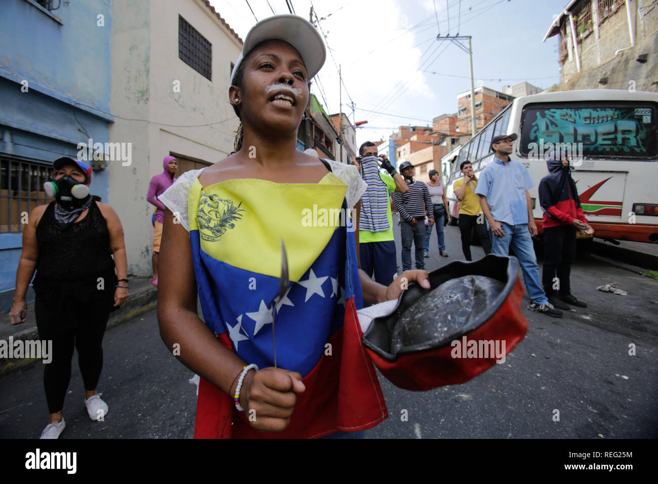 21 January 2019, Venezuela, Caracas: A woman hits a pot with a spoon in a protest in support of a mutiny by national guards against the government of Maduro. Many demonstrators wore toothpaste on their upper lip to defend themselves against tear gas. 'Take to the streets and protest, claim your rights. Here we are to fight for you, for Venezuela,' a national guard had called for a mutiny. Local residents went out into the streets. The mutiny is said to have been suppressed by security forces. The government blamed a conspiracy of right-wing circles for the uprising. Photo: Boris Vergara/dpa Cr - Stock Image