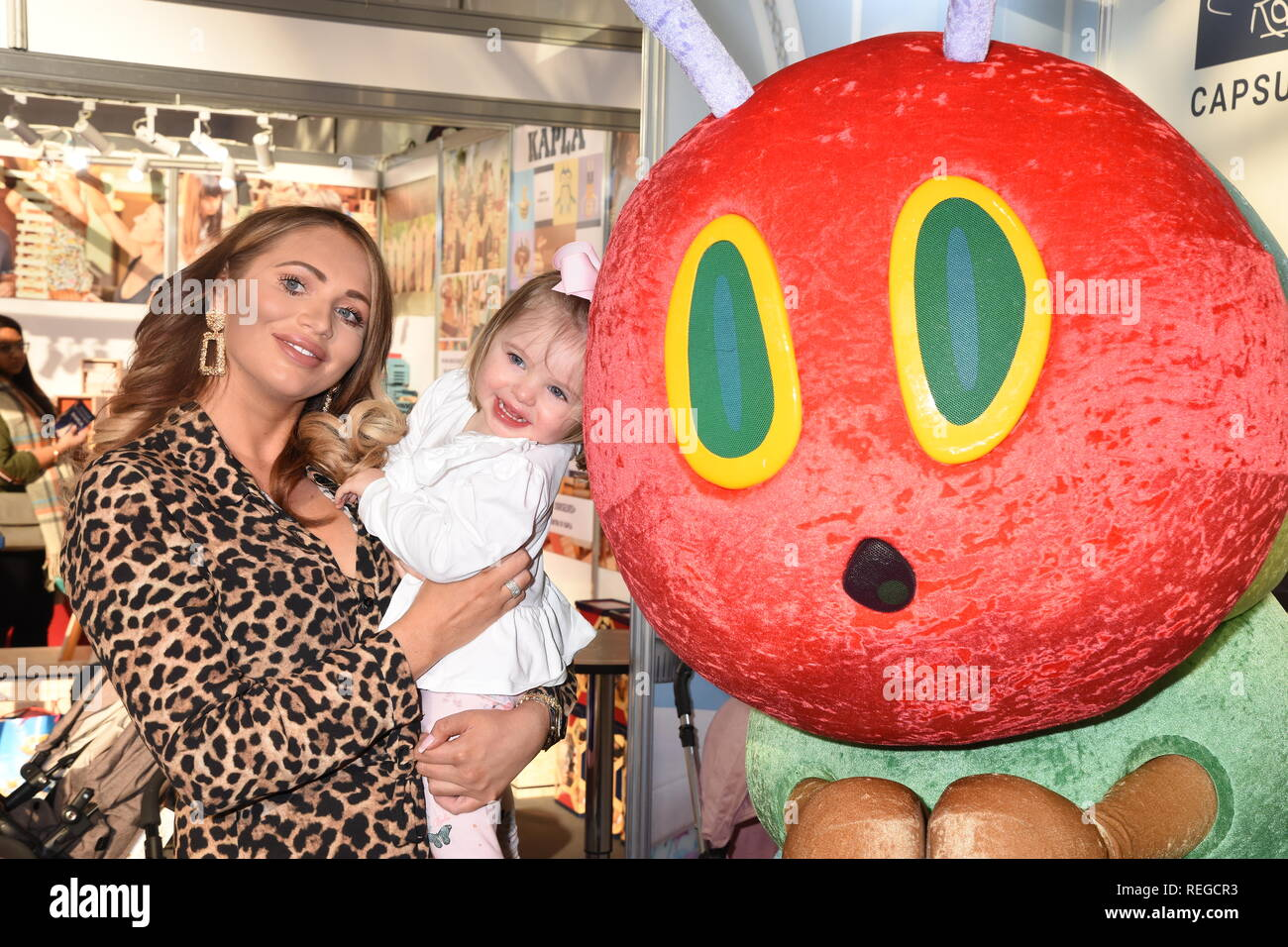 22nd January, 2019. Amy Childs and daughter Polly poses with the Hungry Caterpillar, Roma Pram Stand, The Toy Fair, Olympia, London. UK  Credit: michael melia/Alamy Live News - Stock Image