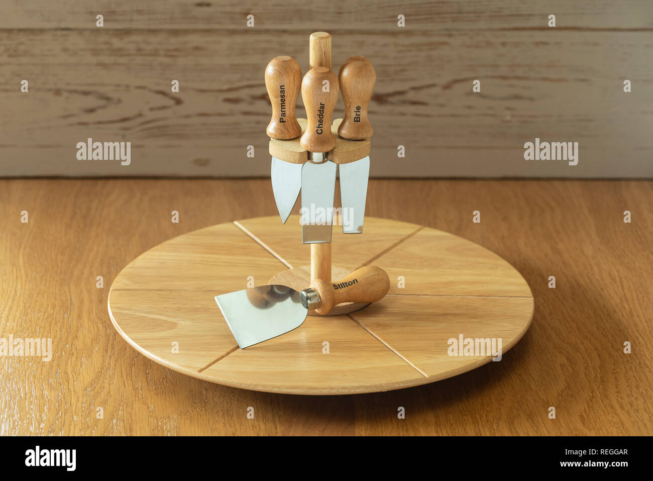 Cheese board and assorted knives. Rotating board for serving cheese and cheese knife. - Stock Image