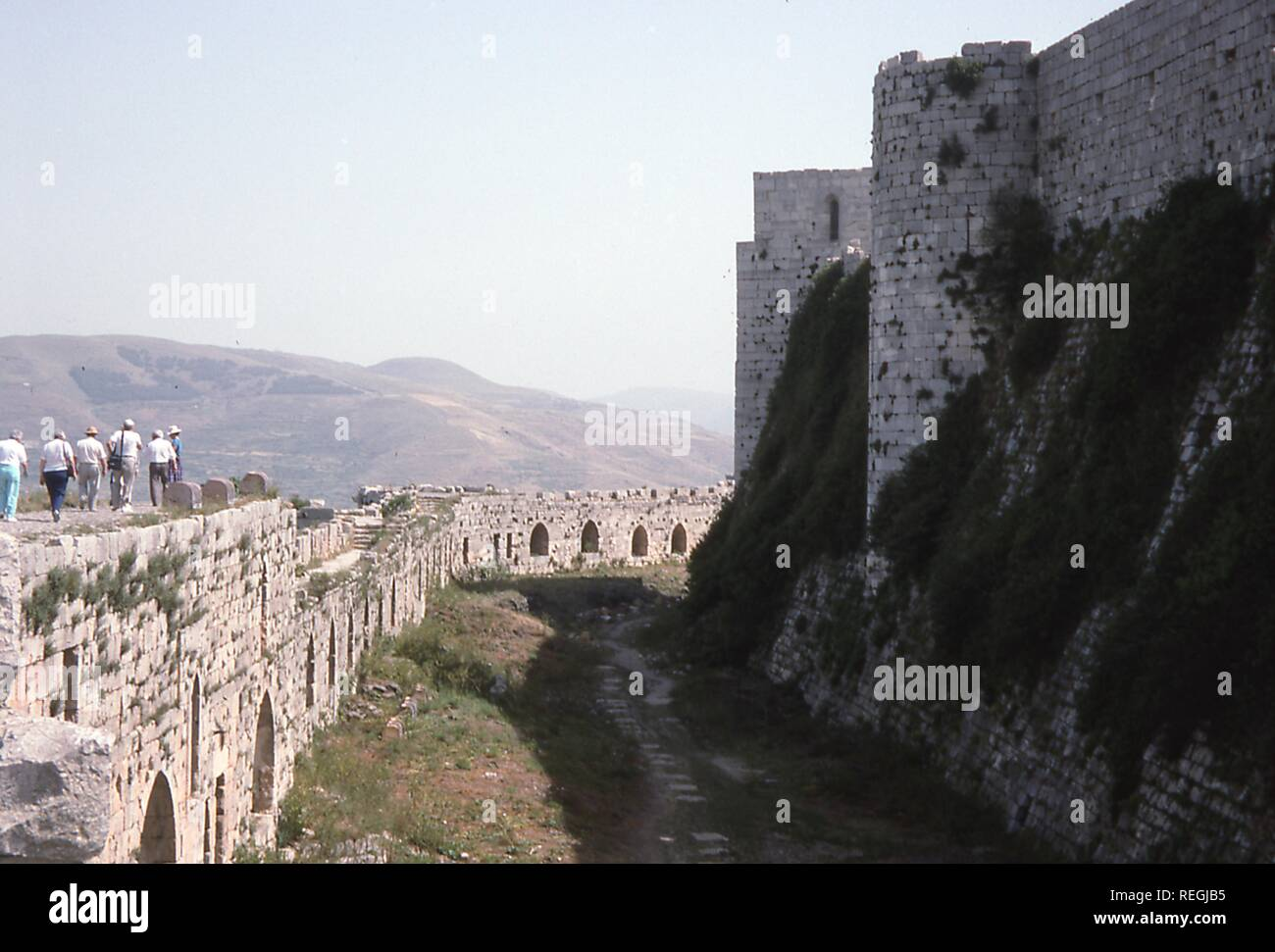 Scene of Western tourists walking the perimeter ramparts at the medieval fortress of Qalaat al-Madiq, Syria, June, 1994. () - Stock Image