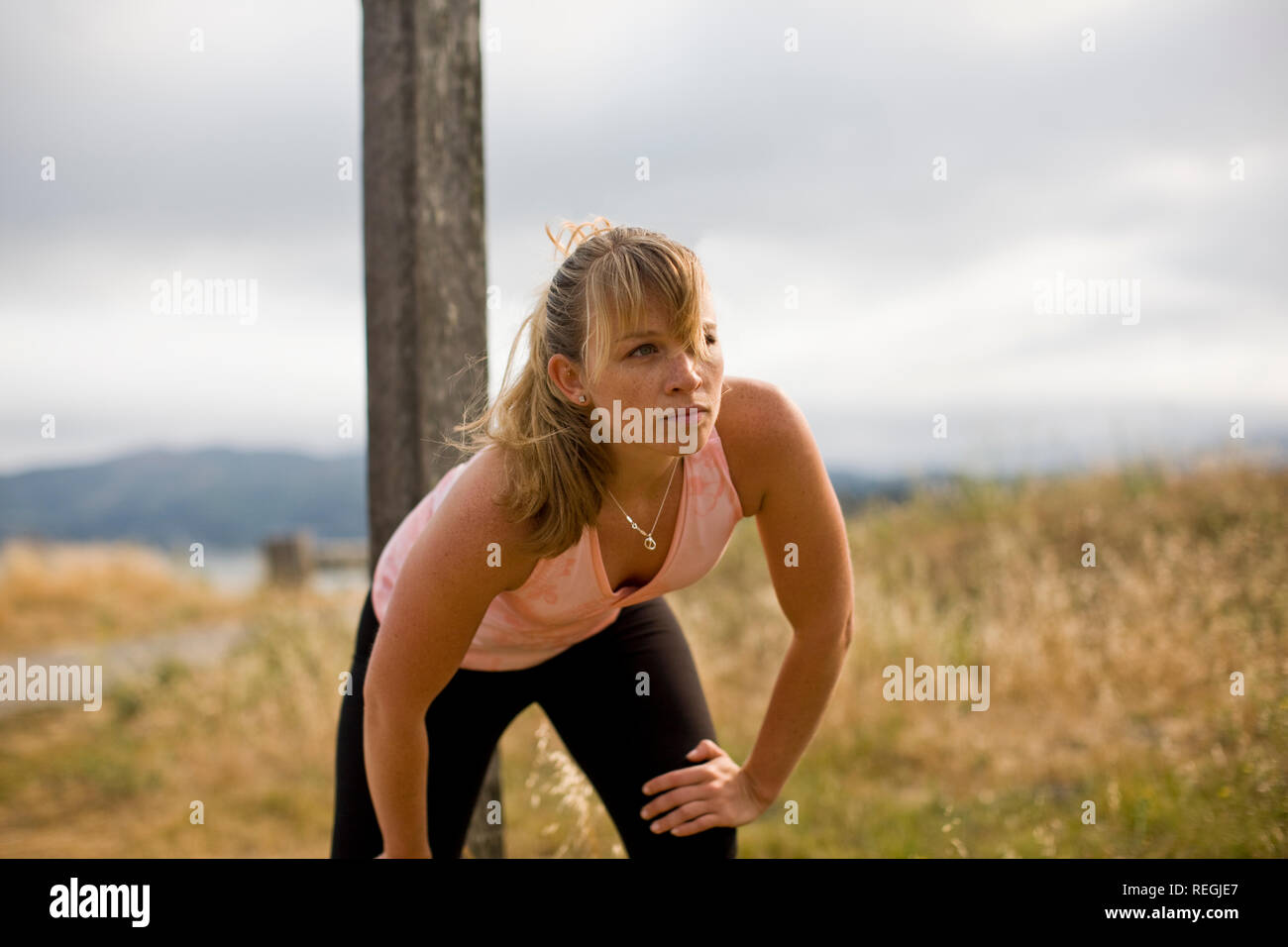 Teenage girl wearing sports gear in a field outside. Stock Photo