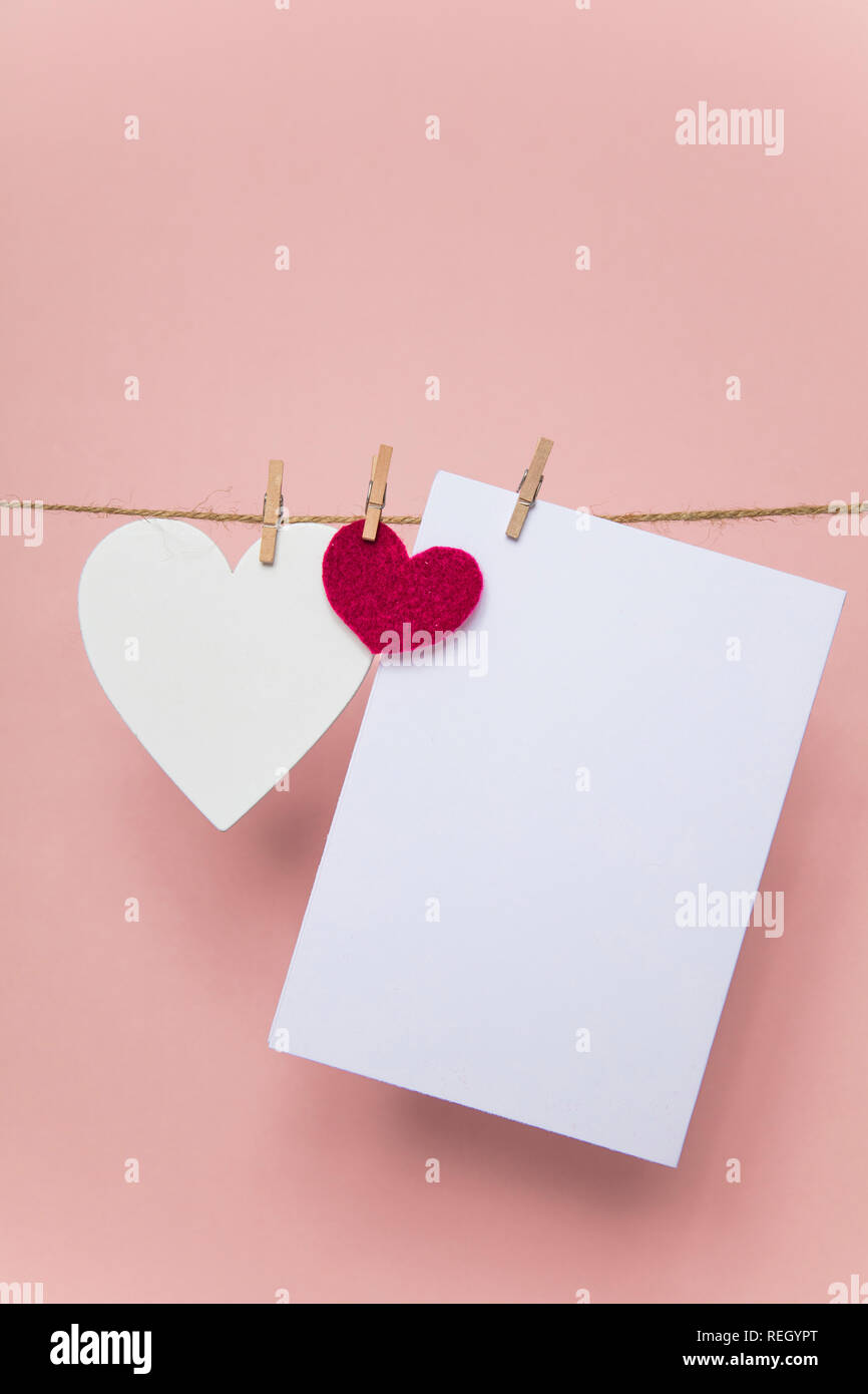 Love letter pegged to a line with red and white hearts. - Stock Image
