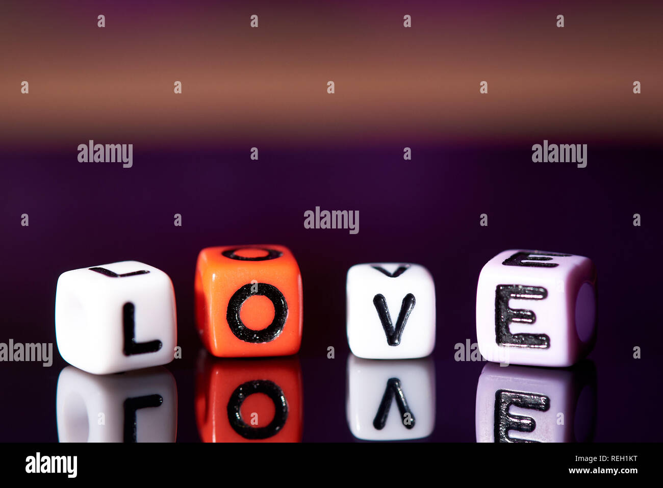 Word love from cubes with reflection on dark blurred background. - Stock Image