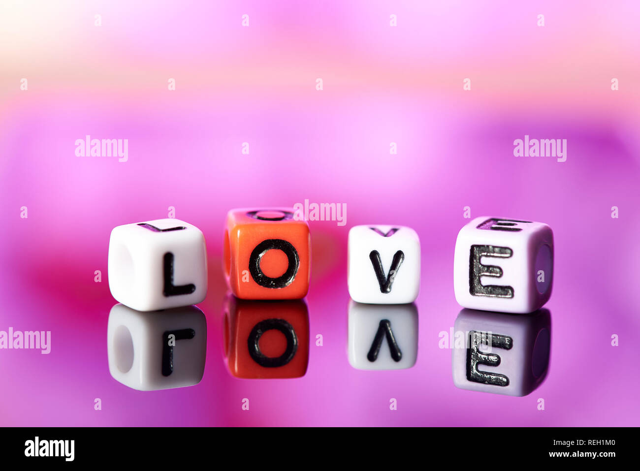 Word love  from cubes with reflection on bright blurred background. - Stock Image