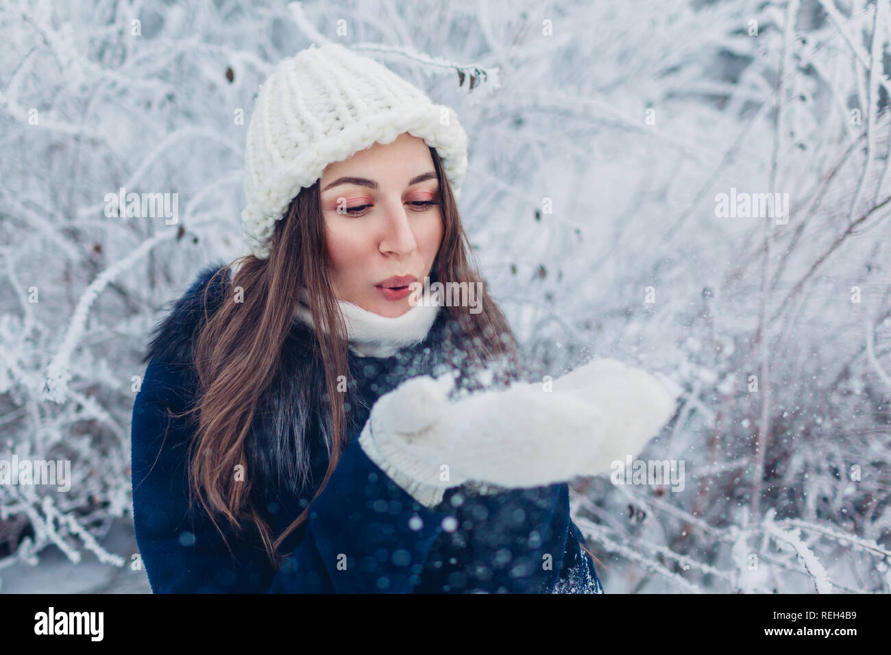 dac36b1d802ce Young woman blowing snow in winter forest. Girl having fun outdoors. Winter  activities -