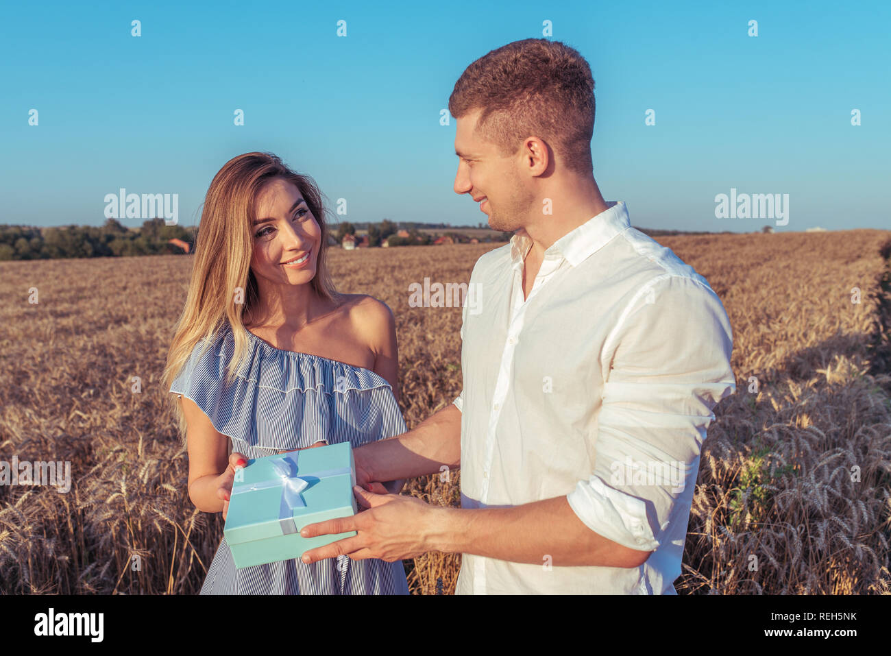 Happy young couple man and woman, adult romantic family. There is sunset in wheat field. Happy smile The guy gives the girl a gift, a bowl box. Concept of happiness, unexpected delight and pleasure. - Stock Image
