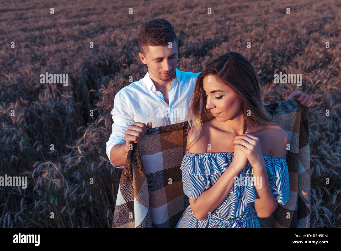 Young couple adult romantic family. Guy hides girl with a warm blanket, in evening it has cooled down. Concept of happiness, tenderness of caring for support of understanding and courting for spouse. - Stock Image