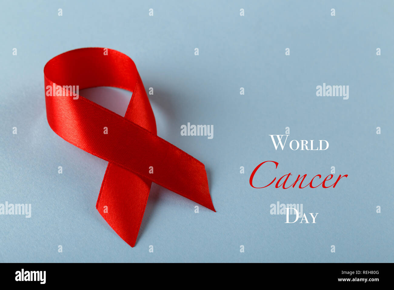 8d8215d9e17 Red ribbon on blue background with text World Cancer Day Stock Photo ...