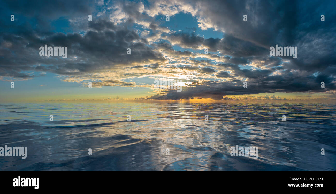Sunset or sunrise reflected on rippling water - Stock Image
