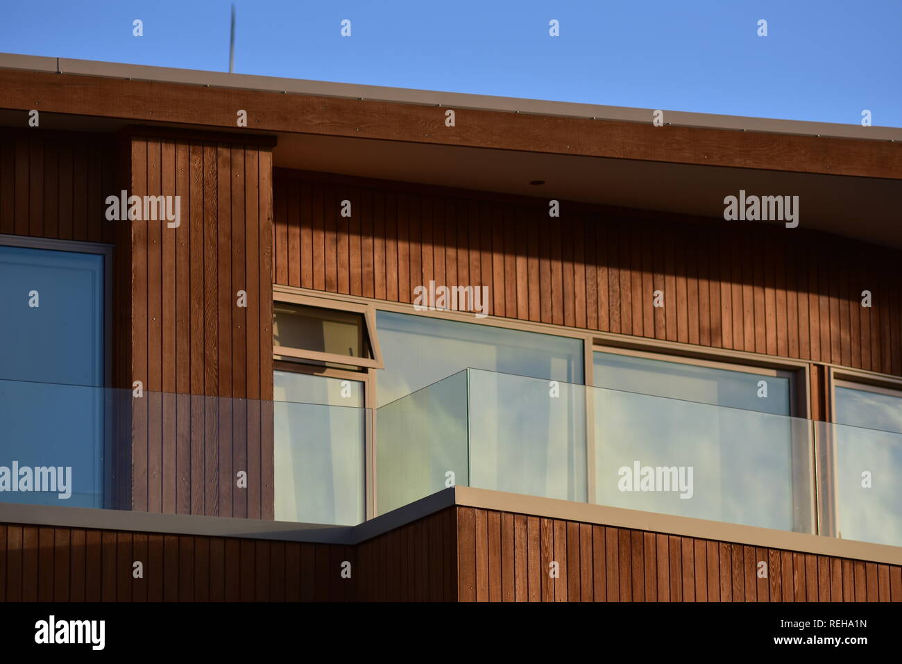 Facade with windows and veranda of modern wooden house with vertical varnished cladding and glass transparent railing. Stock Photo