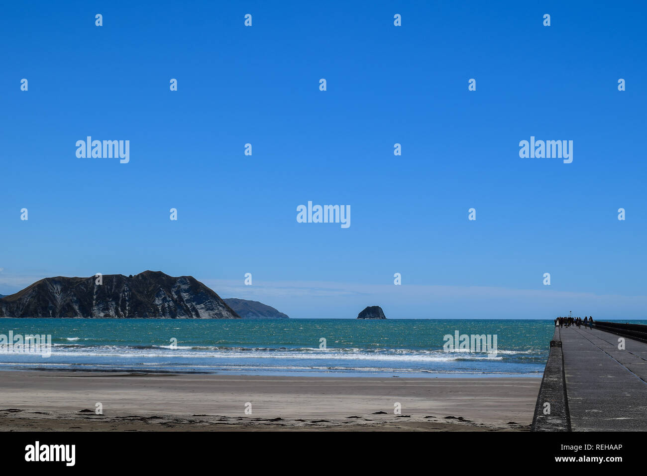 People walk the length of the wharf with the Summer sun above and the calm blue water below in Tolaga Bay, New Zealand - Stock Image