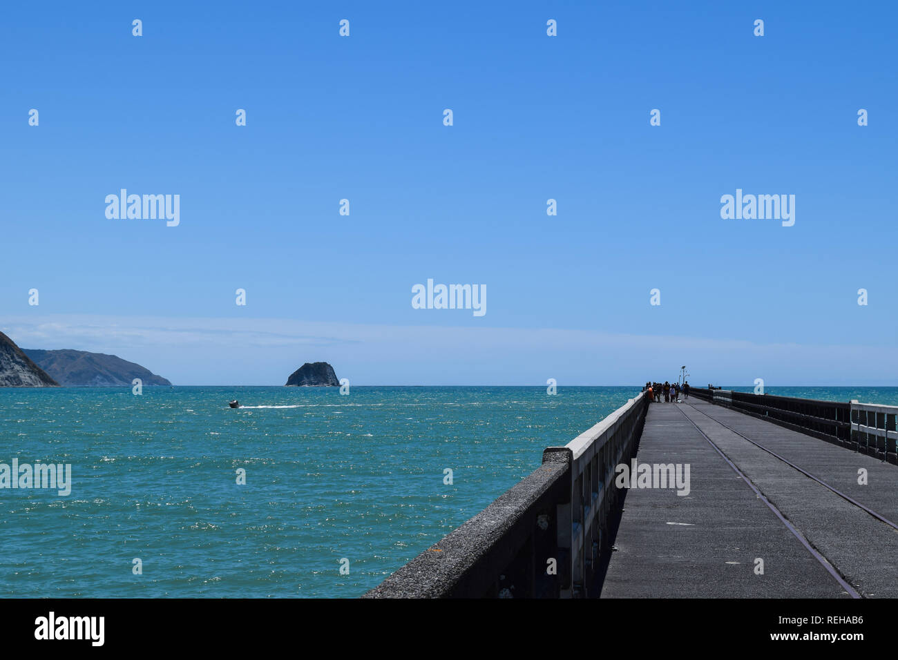 A long shot of the pier as it heads out to sea with the cliffs in the background in Tolaga Bay, New Zealand - Stock Image