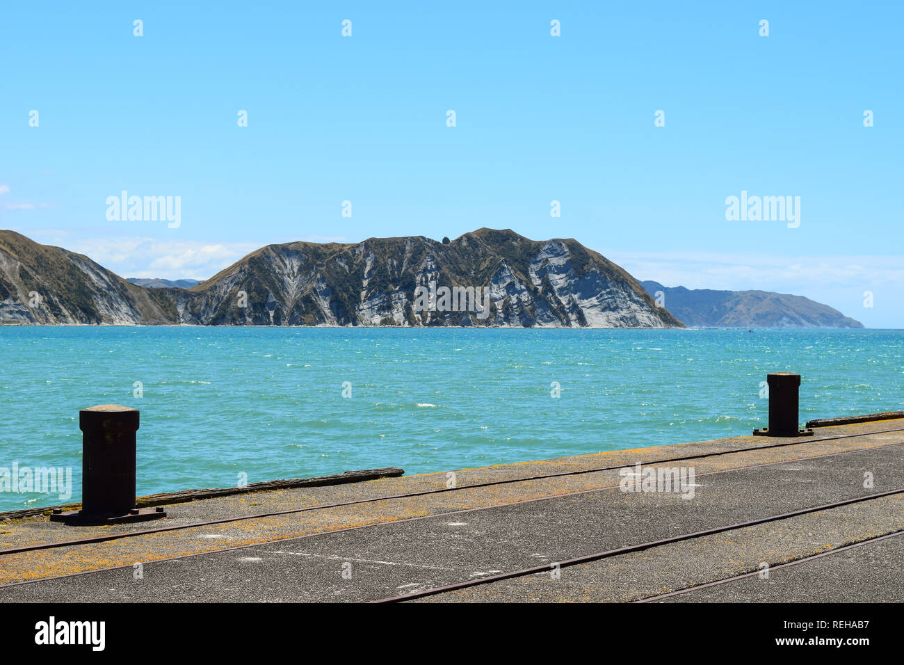 Metal posts along the side of the wharf, with the distant mainland in the background in Tolaga Bay, New Zealand - Stock Image