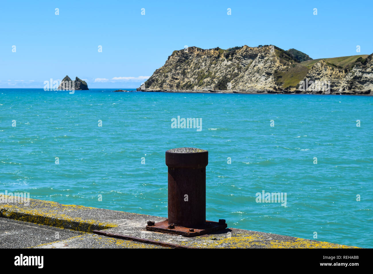 The post at the end of the long walkway along the wharf in Tolaga Bay, New Zealand - Stock Image