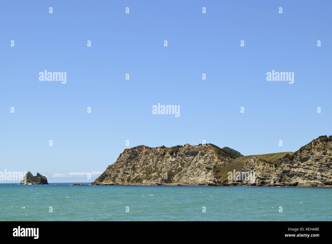 A small island seen at the end of the beach wharf in Tolaga Bay, New Zealand - Stock Image