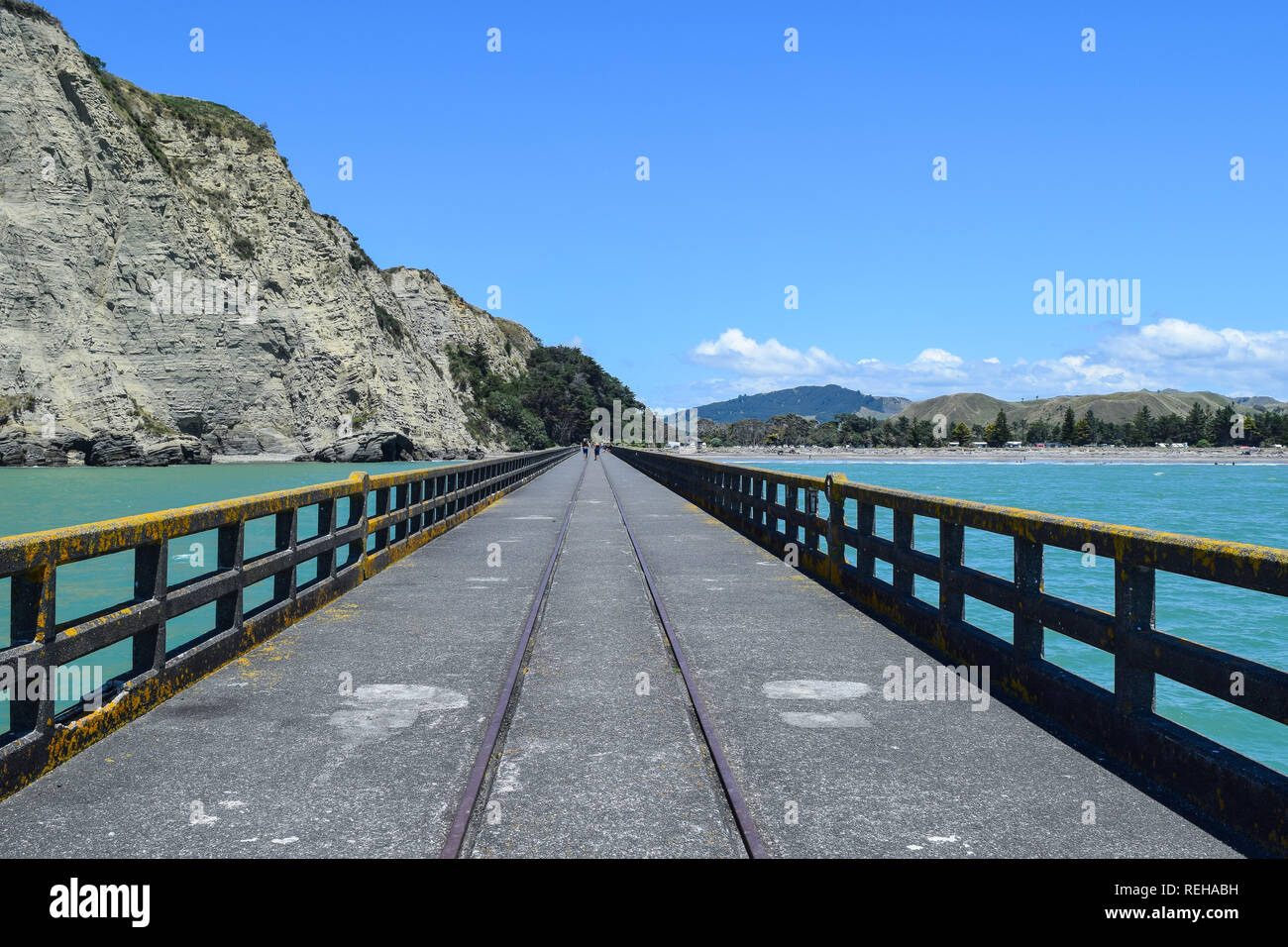 A long straight shot along the concrete wharf over the sand and sea at Tolaga Bay, New Zealand - Stock Image