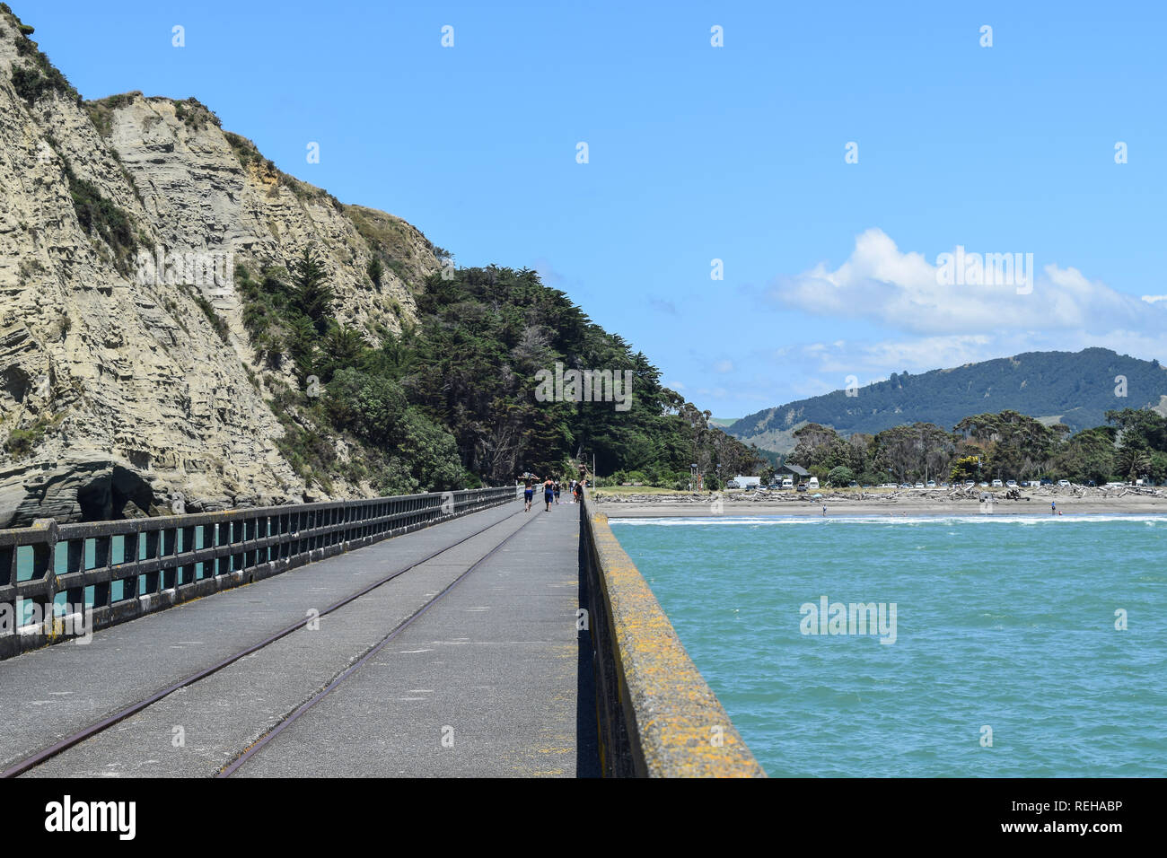 A couple stroll along the long concrete pier in Tolaga Bay, New Zealand - Stock Image