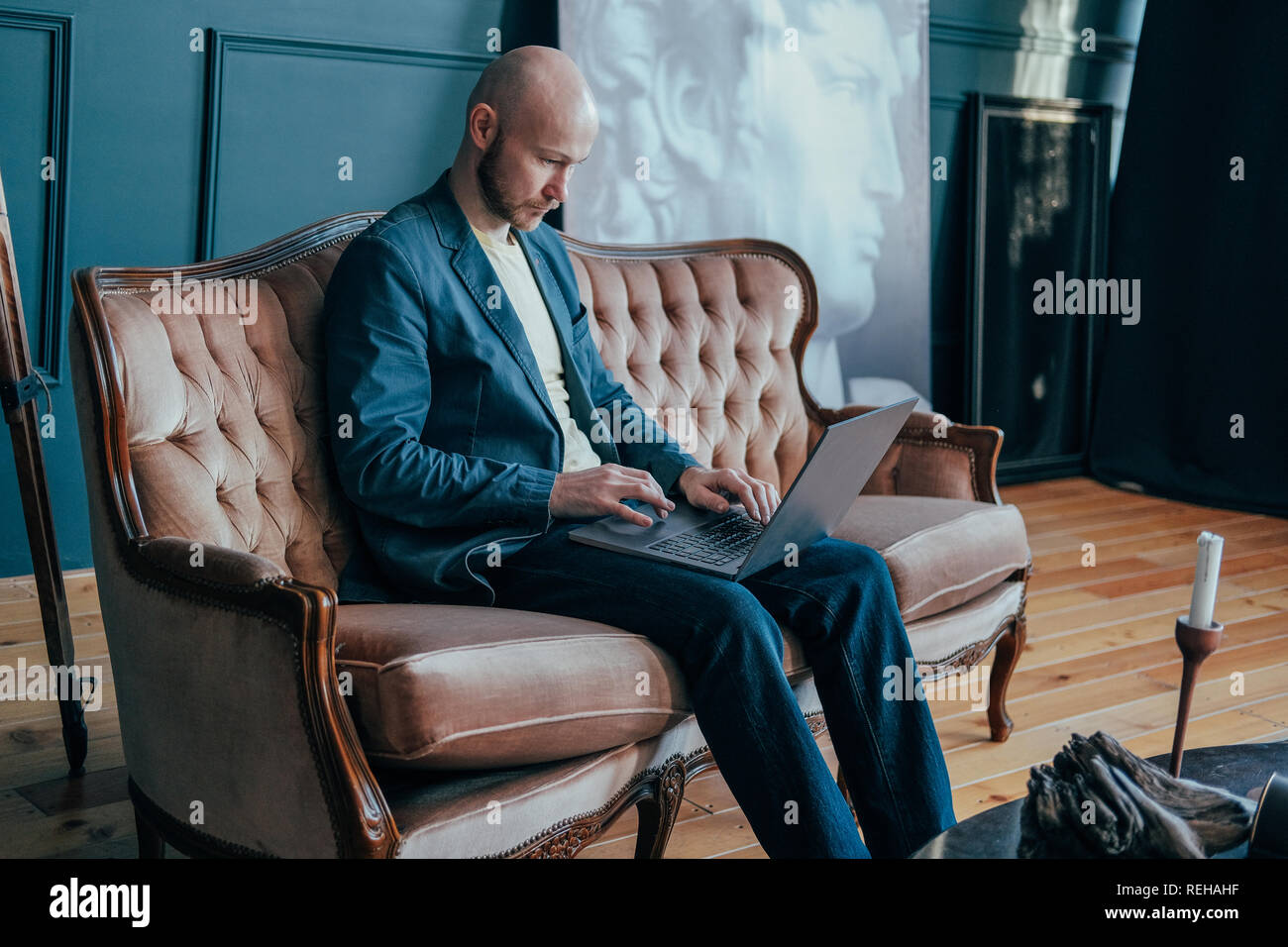 Attractive adult successful surprised bald man with beard in suit working at laptop on his rich cabinet Stock Photo