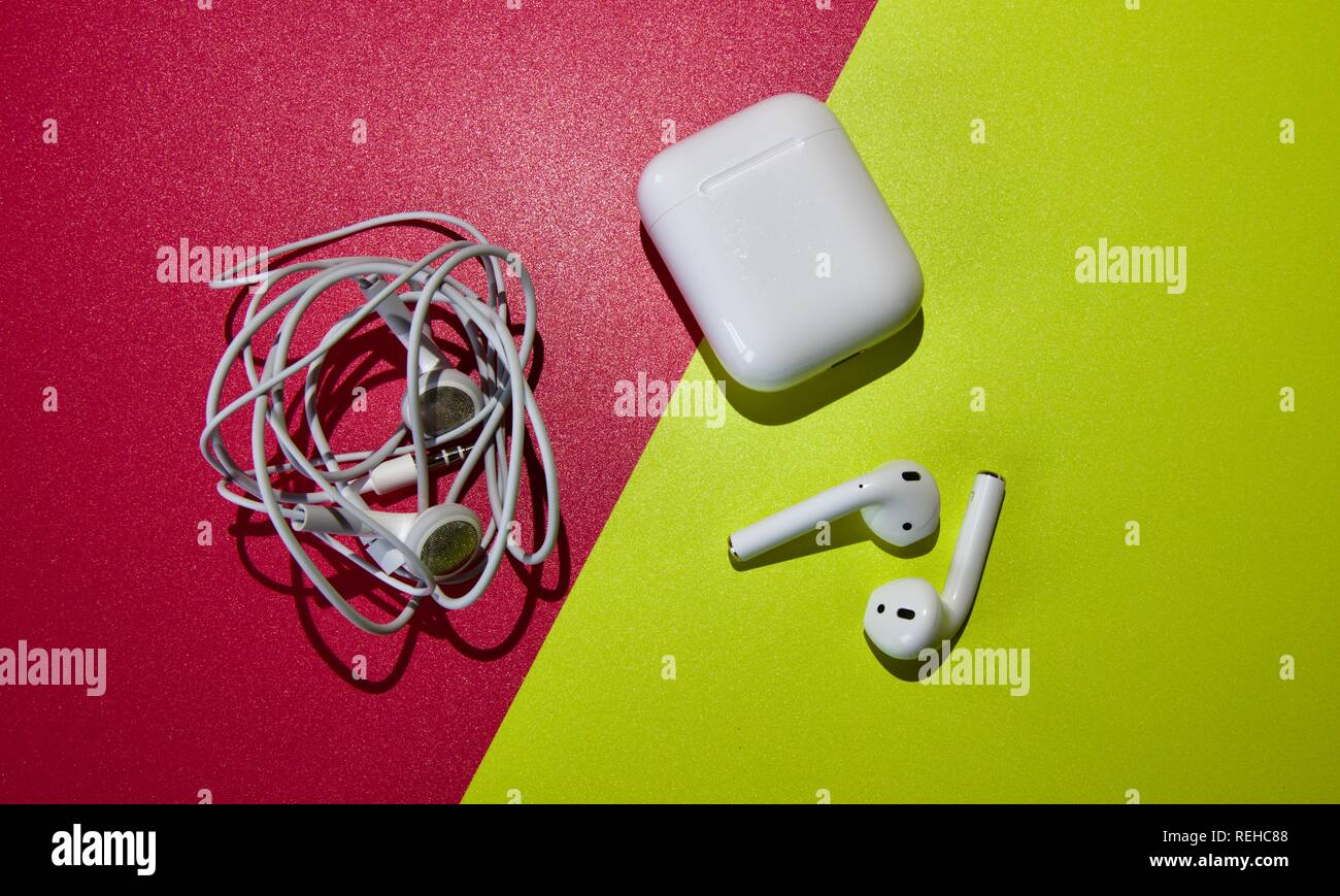 Tangled earbuds and the new wireless AirPods from Apple - Stock Image