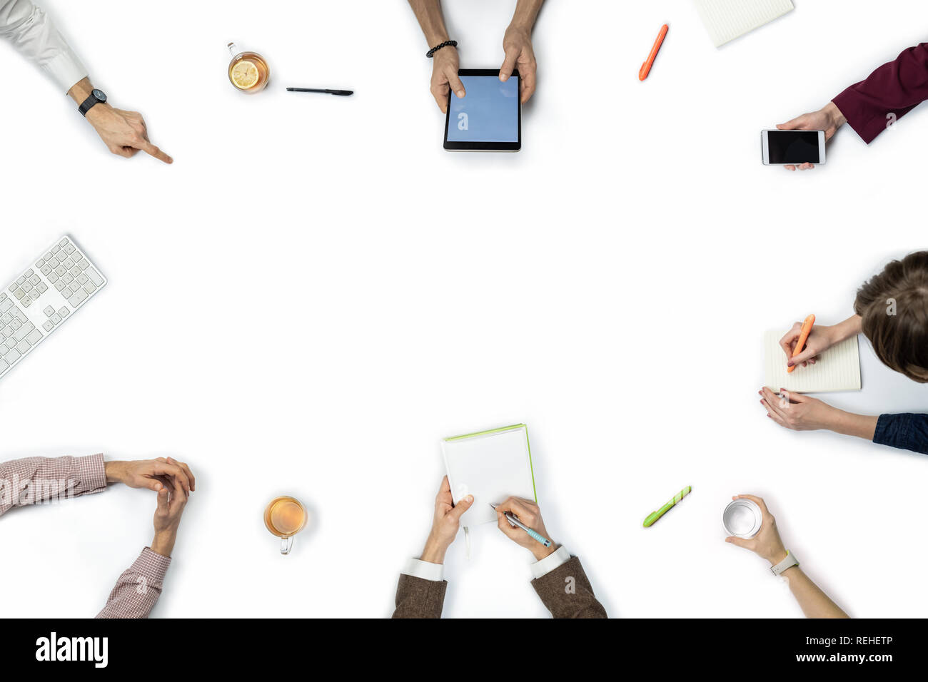 Large group of people at business meeting, top view. Flat lay with copy space of diverse people hands around a table. - Stock Image