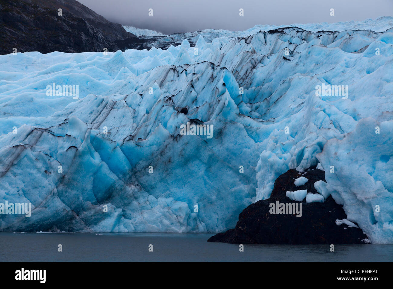 Pinnacles of blue ice march towards the water. Portage Glacier, Alaska - Stock Image