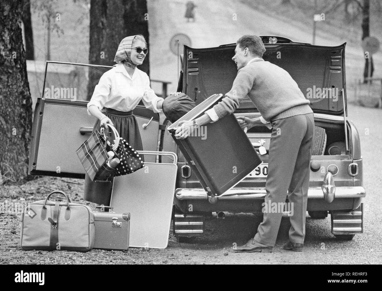 Couple in the 1960s. A young couple are packing the trunk of their car with luggage and camping gear for a car vacation. A practical folding table is also packed. She is dressed in a typical 1950s manor with a white shirt, wide skirt, sunglasses and her hair in a scarf. Sweden 1957 Stock Photo