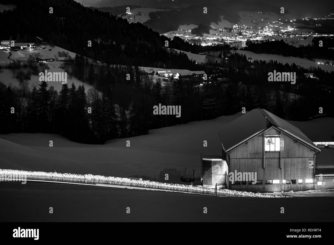 Long exposed night photography of cars driving through a snowy mountain road in the alps of Austria. Stock Photo