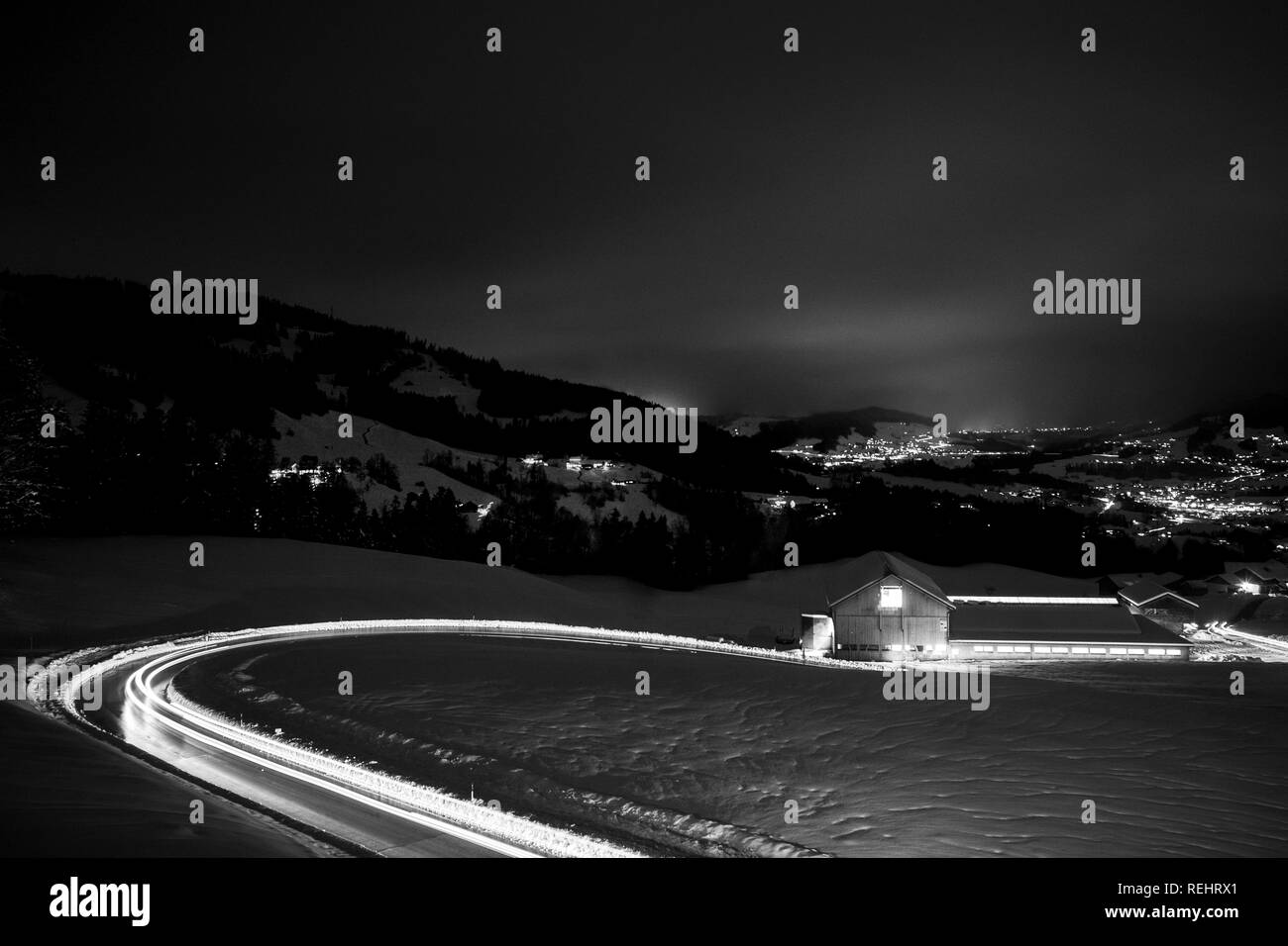 Long exposed night photography of cars driving through a snowy mountain road in the alps of Austria. - Stock Image