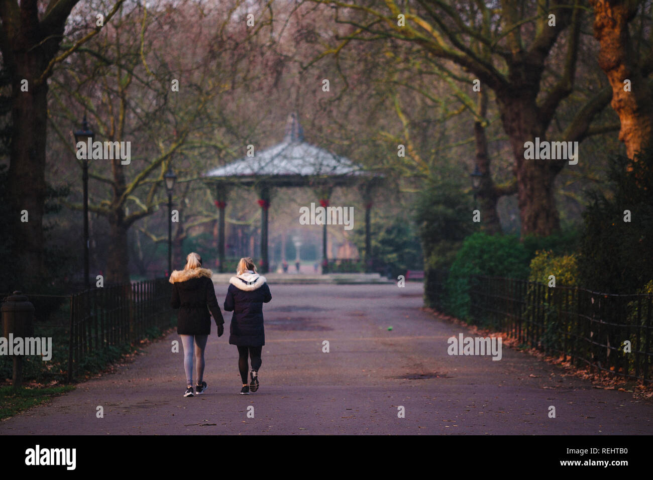Battersea Park's ornate Victorian bandstand in golden hour, with two women walking towards it - Stock Image
