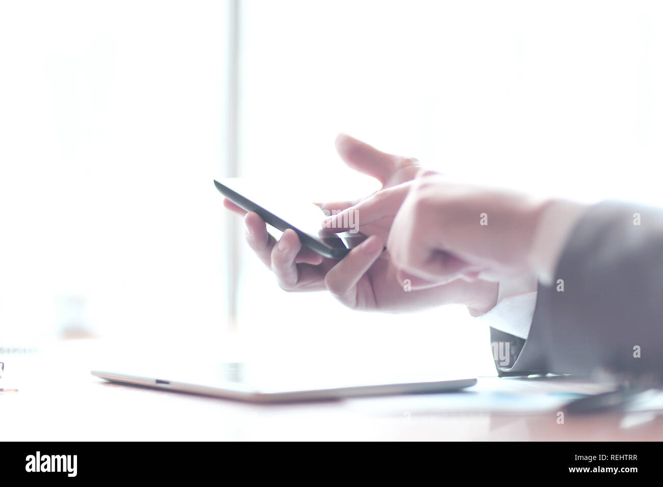 close up.businessman tapping the screen of the smartphone - Stock Image