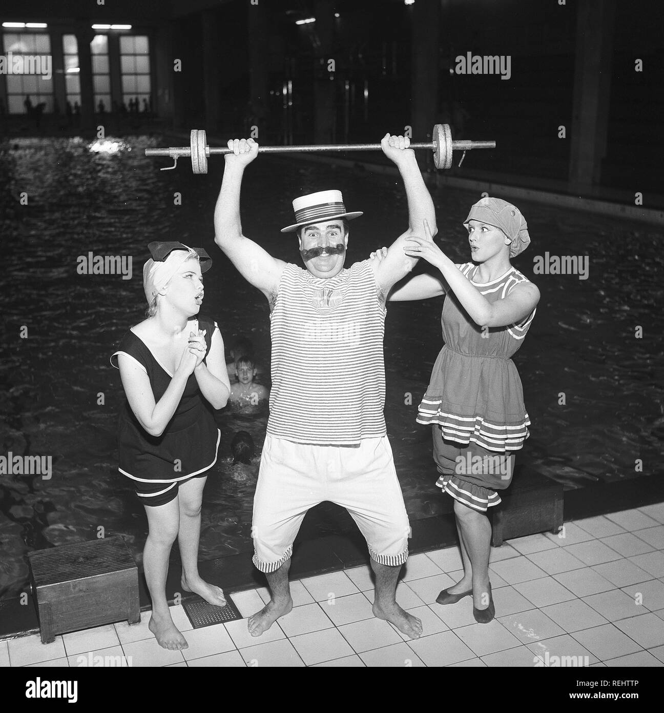 Fun in the 1950s. Two young woman in historical 1920s looking bathingsuits admire the strength of a man lifting a barbell. Although judging from the looks of the weights on it, it appears he's probably not so strong in his arms. Sweden 1950s. Photo Kristoffersson ref BT9-9 - Stock Image