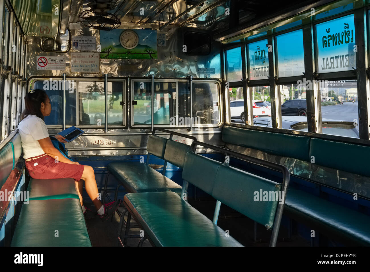 Seen inside a Songthaew (old-time local bus) going from Phuket Town to Patong Beach, Phuket, Thailand, a lone passenger reading on her mobile - Stock Image