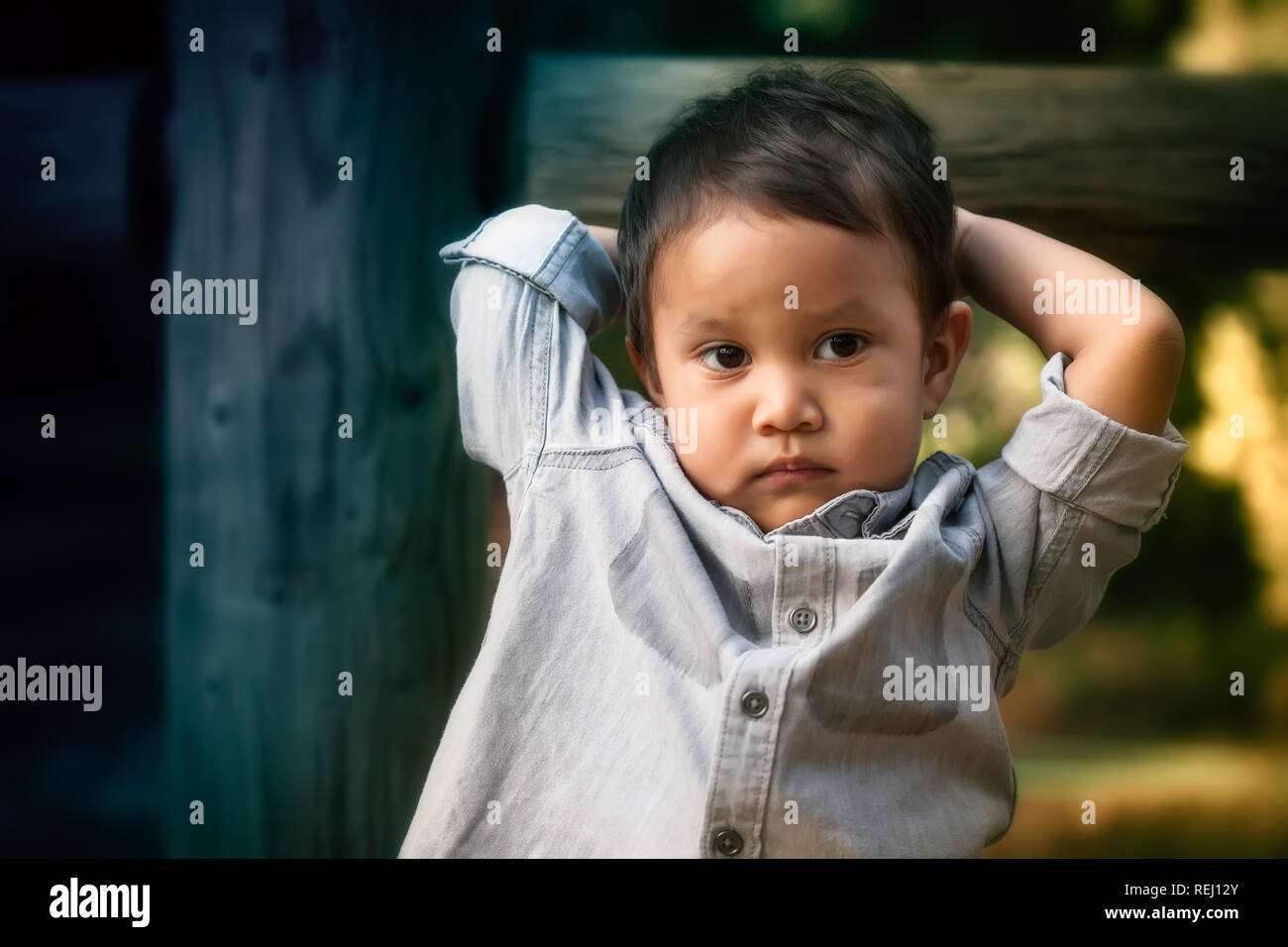 Young toddler boy that looks troubled, worried, or expressing anti social behavior while holding his head with his arms. - Stock Image